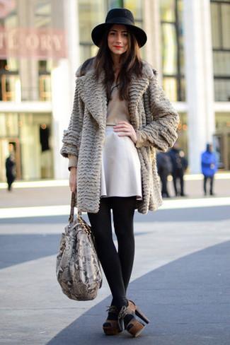 Ce combo d'un t-shirt à manche longue beige et d'une jupe patineuse blanche te permettra de garder un style propre et simple en dehors des horaires de bureau. Une paire de des sandales à talons en daim brunes foncées rendra élégant même le plus décontracté des looks.