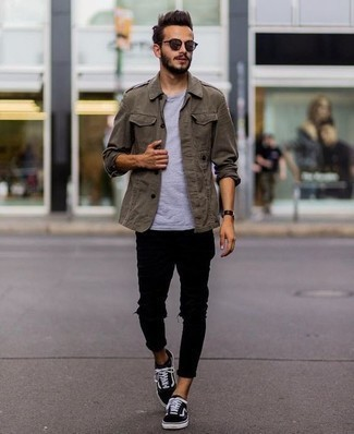 Black Jeans Spring Outfits For Men: Exhibit your chops in men's fashion by wearing this relaxed casual pairing of an olive military jacket and black jeans. Avoid looking too polished by finishing off with black and white canvas low top sneakers. This look is absolutely ideal to welcome springtime.
