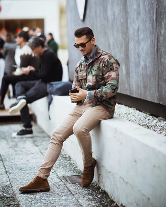 How to wear: olive camouflage military jacket, blue denim shirt, beige skinny jeans, brown suede dress boots
