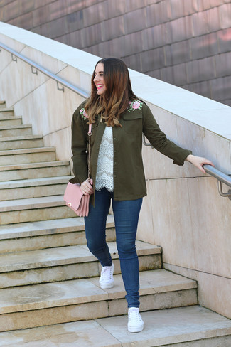 How to Wear White Canvas Low Top Sneakers For Women: An olive embroidered military jacket and navy skinny jeans are both versatile essentials that will integrate nicely within your daily fashion mix. White canvas low top sneakers are a tested footwear style here that's full of character.