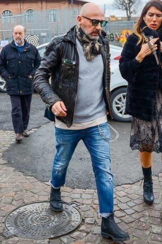 How to Wear Black Leather Chelsea Boots For Men: Such items as a dark brown leather military jacket and blue ripped jeans are an easy way to introduce some cool into your day-to-day lineup. Add black leather chelsea boots to your look for an added touch of style.