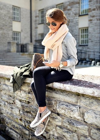 Consider wearing a hunter green military jacket and dark blue skinny jeans for a glam and trendy getup. A pair of grey snake slip-on sneakers will integrate smoothly within a variety of looks. You can be certain this outfit is ideal for fluctuating autumn weather.