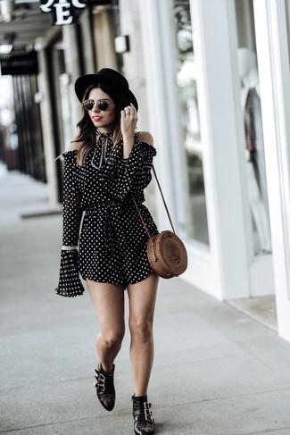 Cómo combinar: mono corto a lunares en negro y blanco, botines de cuero con tachuelas negros, bolso bandolera de paja marrón, sombrero de lana negro