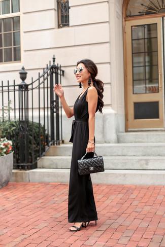 Cómo combinar: mono negro, sandalias de tacón de cuero negras, bolso de hombre de cuero acolchado negro, gafas de sol plateadas