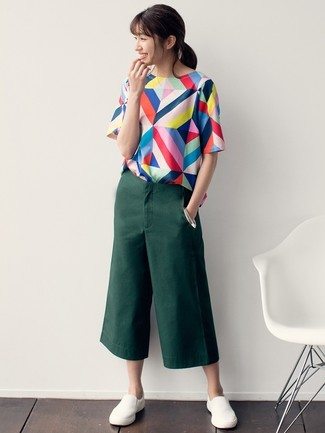 How to Wear White Slip-on Sneakers For Women: This laid-back pairing of a multi colored geometric short sleeve blouse and dark green culottes is super easy to pull together without a second thought, helping you look chic and prepared for anything without spending too much time searching through your closet. If you wish to effortlesslly tone down this look with footwear, complete this look with a pair of white slip-on sneakers.