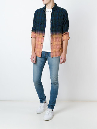 Blue Skinny Jeans Warm Weather Outfits For Men: A multi colored plaid long sleeve shirt and blue skinny jeans are great menswear must-haves to integrate into your daily arsenal. Lift up your look with white canvas low top sneakers.