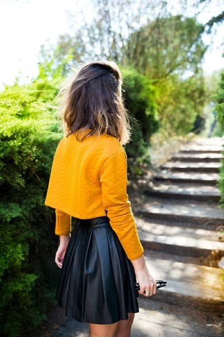 This pairing of an orange cropped top and a black pleated leather mini skirt will set you apart effortlessly.