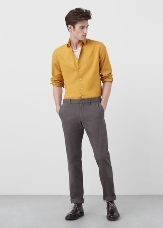 How to Wear Boots For Men: Extra stylish, this casual combination of a mustard long sleeve shirt and grey chinos offers variety. Boots will immediately spruce up even the laziest of outfits.