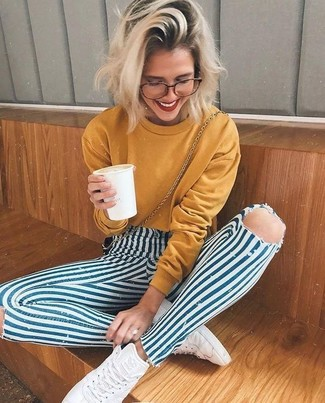 How to wear: mustard sweatshirt, white and blue vertical striped skinny jeans, white leather high top sneakers