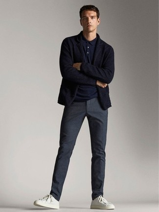 Navy Polo Outfits For Men: A navy polo and navy chinos are a pairing that every modern gentleman should have in his casual wardrobe. White canvas low top sneakers work wonderfully well within this outfit.