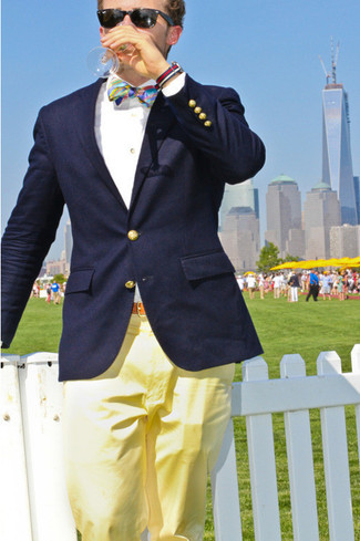 Make a stylish entry anywhere you go in a dark blue blazer and yellow chino pants. This combination has all the potential to become your summer go-to.