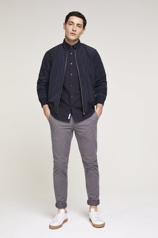 Men's Outfits 2020: Combining a navy bomber jacket with grey chinos is a good choice for a cool and casual outfit. If you need to instantly tone down your ensemble with shoes, add a pair of white canvas low top sneakers to the equation.