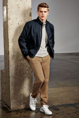 How to Wear Khaki Chinos: Go for a straightforward but at the same time casually dapper choice by wearing a navy bomber jacket and khaki chinos. Give a dressed-down twist to an otherwise mostly classic look by rounding off with white and black leather low top sneakers.