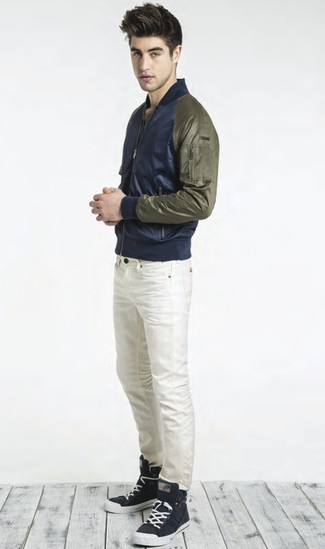 Look stylish yet practical in a dark blue bomber jacket and white skinny jeans. Monochrome high top sneakers will contrast beautifully against the rest of the look. With springtime coming, it's time to sport simple and stylish combinations, just like this one.