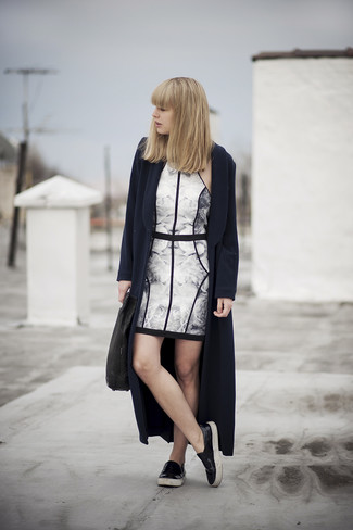Opt for a navy blue coat and a white and black floral bodycon dress for both chic and easy-to-wear look. A pair of black leather slip-on sneakers will be a stylish addition to your outfit.