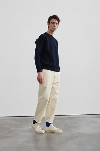 Men's Looks & Outfits: What To Wear In Warm Weather: A navy crew-neck sweater and beige chinos are stylish menswear pieces, without which our closets would be incomplete. Take an otherwise mostly dressed-up ensemble in a more relaxed direction by finishing off with a pair of beige canvas low top sneakers.