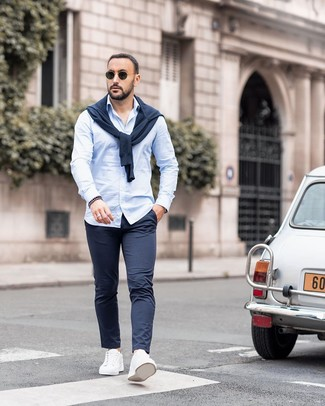How to wear: navy crew-neck sweater, light blue long sleeve shirt, navy chinos, white leather low top sneakers