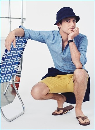 How to wear: navy crew-neck sweater, light blue chambray long sleeve shirt, yellow shorts, brown flip flops