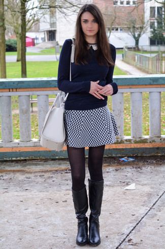 Opt for a navy blue crew-neck jumper and a white and black gingham skater skirt for a casual coffee run. Elevate your getup with black leather knee high boots.