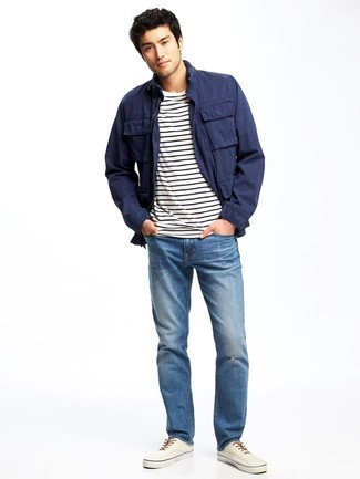 How to Wear White Plimsolls For Men: Wear a navy field jacket and blue jeans for both stylish and easy-to-achieve outfit. The whole outfit comes together brilliantly if you complement your ensemble with a pair of white plimsolls.