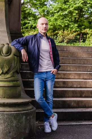 How to wear: navy harrington jacket, beige crew-neck t-shirt, blue jeans, white leather low top sneakers