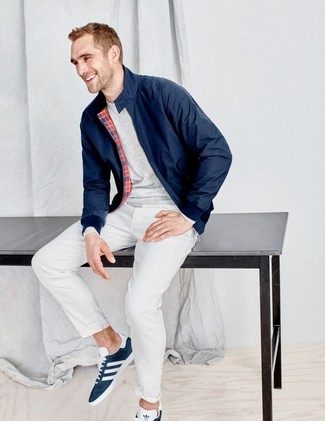 How to wear: navy harrington jacket, grey long sleeve t-shirt, white chinos, navy suede low top sneakers