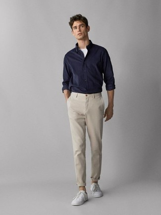 Men's Looks & Outfits: What To Wear In 2020: This relaxed pairing of a navy long sleeve shirt and beige chinos is very easy to throw together without a second thought, helping you look stylish and prepared for anything without spending a ton of time combing through your wardrobe. Rounding off with a pair of white low top sneakers is an effective way to introduce a dash of stylish effortlessness to this outfit.