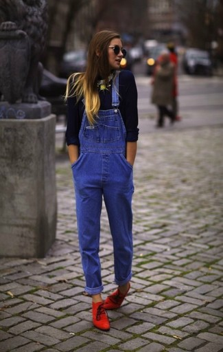 A navy blue long sleeve t-shirt and blue denim dungarees feel perfectly suited for weekend activities of all kinds. A cool pair of red suede ankle boots is an easy way to upgrade your look.