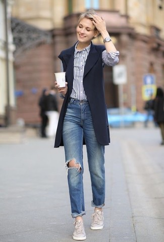 How to Wear Blue Ripped Boyfriend Jeans: If you're a fan of off-duty combinations, then you'll like this combination of a navy sleeveless coat and blue ripped boyfriend jeans. Our favorite of a variety of ways to round off this outfit is grey leather low top sneakers.