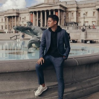 Beige Canvas Low Top Sneakers Outfits For Men: A navy suit and a black hoodie will add sophisticated style to your current lineup. In the shoe department, go for something on the casual end of the spectrum by sporting a pair of beige canvas low top sneakers.
