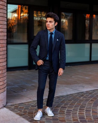 How to wear: navy vertical striped wool suit, blue denim shirt, white canvas low top sneakers, black tie