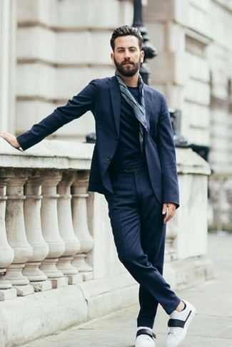 How to Wear a Navy Suit: For an effortlessly smart outfit, pair a navy suit with a navy crew-neck t-shirt — these two pieces fit wonderfully together. Introduce a pair of white and black leather low top sneakers to the equation to keep the getup fresh.
