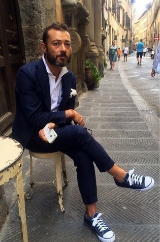 White Polo Outfits For Men: For an outfit that's very straightforward but can be styled in a great deal of different ways, dress in a white polo and a navy suit. Serve a little outfit-mixing magic with navy and white canvas low top sneakers.