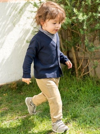 How to Wear a Navy Cardigan For Boys: Teach your munchkin to take pride in his appearance by suggesting that he go for a navy cardigan and tan trousers. Grey sneakers are a nice choice to complete this look.