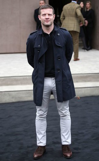 Dermot O'Leary wearing Navy Trenchcoat, Black Polo, White Chinos, Dark Brown Suede Oxford Shoes