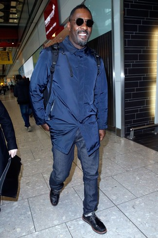 Idris Elba wearing Navy Trenchcoat, Navy Jeans, Black Leather Desert Boots, Navy Backpack