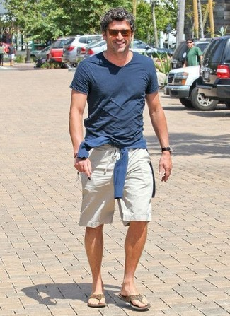 Brown Flip Flops Outfits For Men: Pair a navy v-neck sweater with beige shorts for a simple getup that's also pieced together nicely. Complete this ensemble with a pair of brown flip flops to keep the ensemble fresh.