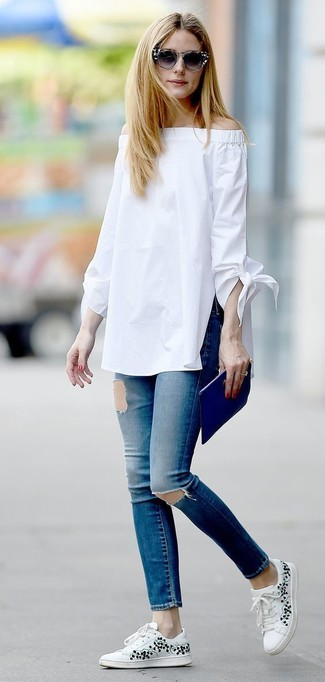 Olivia Palermo wearing White Off Shoulder Top, Blue Ripped Skinny Jeans, White Floral Low Top Sneakers, Blue Leather Clutch