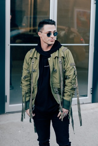 How to wear: olive bomber jacket, black and white print hoodie, black ripped skinny jeans, black sunglasses