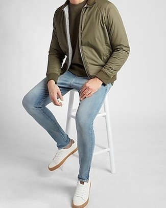 Olive Bomber Jacket Outfits For Men: Wear an olive bomber jacket and light blue skinny jeans to assemble an interesting and modern-looking casual ensemble. Add white leather low top sneakers to the mix and off you go looking dashing.