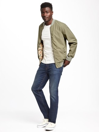 How to Wear White Plimsolls For Men: This pairing of an olive bomber jacket and navy jeans is a safe go-to for a ridiculously stylish getup. Let your sartorial savvy really shine by finishing off your ensemble with a pair of white plimsolls.