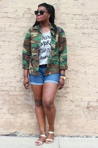 How to wear: olive camouflage military jacket, white and black print crew-neck t-shirt, blue denim shorts, gold leather flat sandals