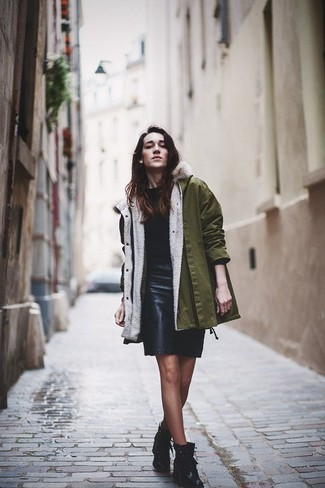 How to wear: olive parka, black crew-neck sweater, black leather pencil skirt, black leather lace-up flat boots