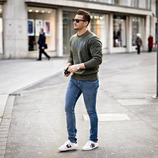 How to wear: olive print sweatshirt, blue skinny jeans, white print leather low top sneakers