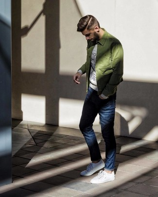 How to wear: olive shirt jacket, grey print sweatshirt, navy jeans, white low top sneakers