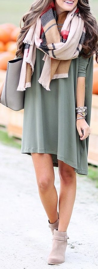 This pairing of an olive sweater dress and a multi colored scarf is impeccably stylish and yet it looks cozy and ready for anything. Grey suede booties are a wonderful choice to round off the look. It's is a good idea when it comes to an awesome transition outfit.