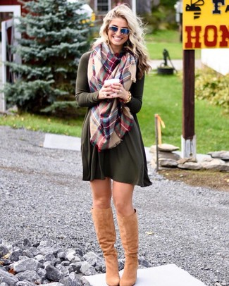 Look awesome without really trying in an olive sweater dress and a multi colored scarf. This look is complemented perfectly with camel suede knee high boots. Rest assured, this getup will keep you snug as well as looking cute in this awkward fall weather.