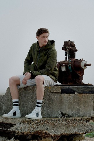How to wear: olive windbreaker, beige shorts, white leather low top sneakers, white and black horizontal striped socks