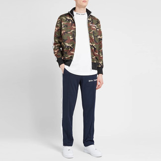 White and Red Leather Low Top Sneakers Outfits For Men: If it's ease and functionality that you love in a look, team an olive camouflage zip sweater with navy sweatpants. Play down the casualness of your look by finishing off with white and red leather low top sneakers.