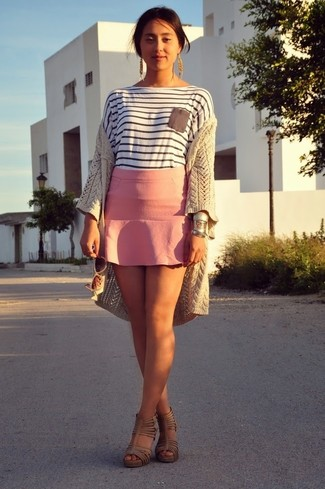 Consider pairing a beige knit open cardigan with a dusty pink mini skirt for a Sunday lunch with friends. Dress up this look with khaki leather heeled sandals.